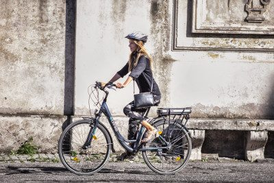 Blonde Italian girl tiding e-bike in Rome
